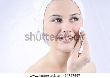 Close-up portrait of young beautiful woman with cotton swab cleaning her face - stock photo