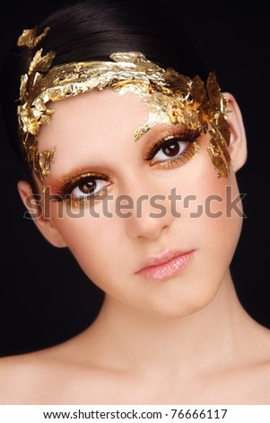 Close-up portrait of young beautiful woman with fancy golden make-up - stock photo