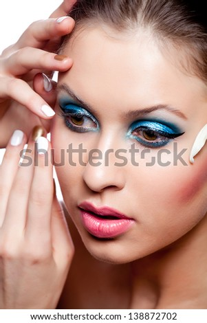 Close-up portrait of young beautiful woman with make-up over white studio shot