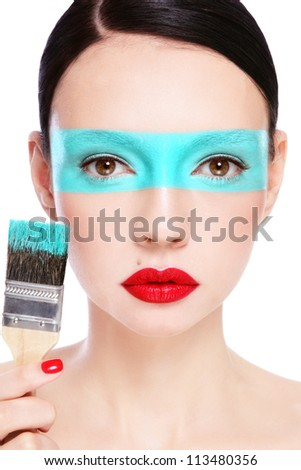 Close-up portrait of young beautiful woman with painted face and brush, on white background