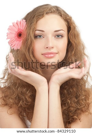 Close-up portrait of young beautiful woman with pink flower in her hair holding her hands near the face . Isolated on white background - stock photo