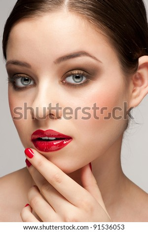Close-up portrait of young beautiful woman with red lipstick and manicure - stock photo