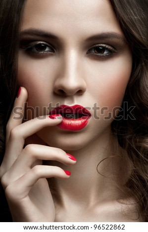 Close-up portrait of young beautiful woman with red lipstick, red manicure and smoky eyes