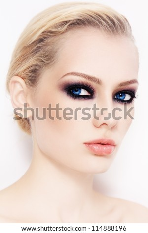 Close-up portrait of young beautiful woman with smoky eyes, on white wall - stock photo