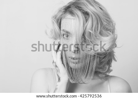 Close-up portrait of young beautiful woman with smoky make-up and chains over her face - stock photo