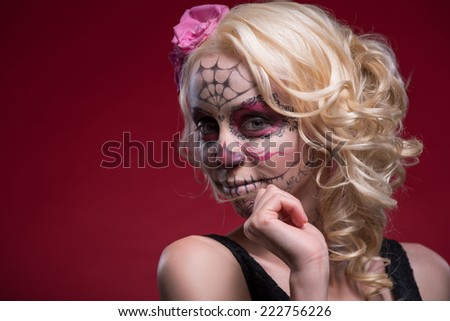 Close-up portrait of young blond girl with lightly smiling face with Calaveras makeup and a rose flower in her hair looking confident at the camera isolated on red background with copy place - stock photo