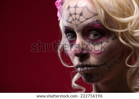 Close-up portrait of young blond girl with sad face with Calaveras makeup and a rose flower in her hair upset looking at the camera isolated on red background with copy place - stock photo