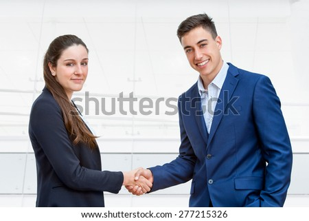 Close up portrait of young business couple dressed in suits shaking hands with office in background.