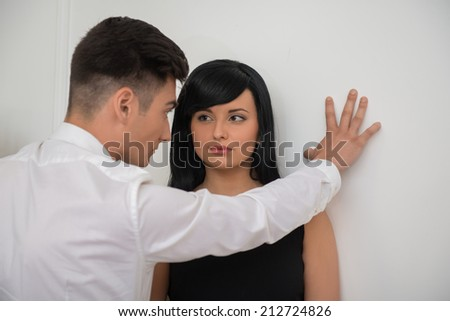 Close-up portrait of young business couple in passion looking to each other near the wall, man keep his hand over a beautiful woman - stock photo