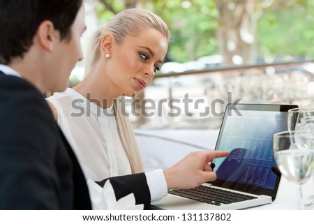 Close up portrait of young business couple reviewing work on laptop at lunch. - stock photo