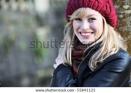 Close up portrait of young caucasian woman outdoors, leaning against a tree - stock photo