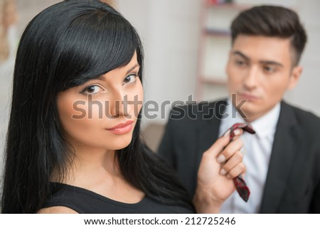 Close-up Portrait of young charming businesswoman flirting and pulling her colleague by the tie in office, looking at the camera