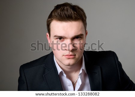 Close-up portrait of young confident businessman on a gray background