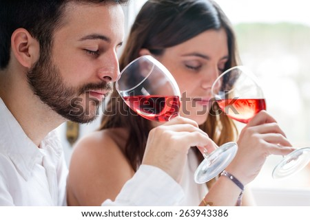 Close up portrait of young couple at wine tasting. Man and woman smelling wine with eyes closed. - stock photo