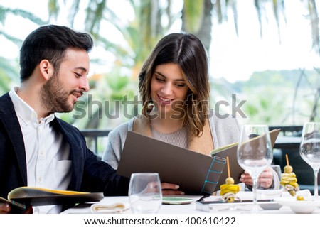 Close up portrait of young couple looking at restaurant menu in Hotel. - stock photo