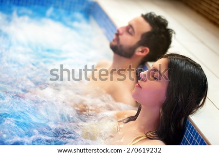 Close up portrait of young couple relaxing in spa jacuzzi. Couple together in bubble water with eyes closed. - stock photo