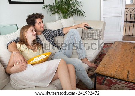 Close up portrait of young couple sitting together on a sofa at home watching television, joyfully smiling eating pop corn enjoying a night in together. Home lifestyle and entertainment technology. - stock photo
