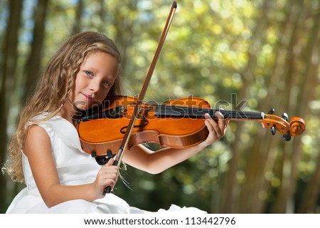 Close up portrait of young cute violinist playing in the woods. - stock photo