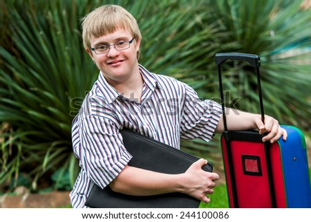 Close up portrait of young Down syndrome student with file and trolley. - stock photo