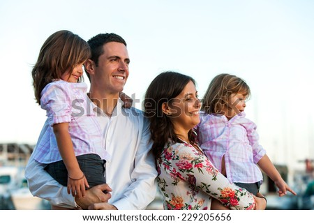 Close up portrait of young family with two little daughters looking into the distance at sunset. - stock photo