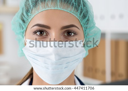 Close up portrait of young female surgeon doctor or intern wearing protective mask and hat. Healthcare, medical education, emergency medical service, surgery or veterinary concept - stock photo