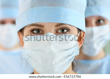 Close-up portrait of young female surgeon doctor surrounded by her team. Group of surgeon in operation theatre. Healthcare, medical education, emergency medical service and surgery concept - stock photo