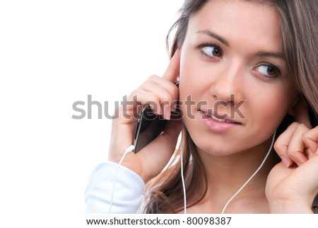 Close-up portrait of young girl listening, enjoying music and holding cellular and talking on mobile phone in earphones isolated on white background - stock photo