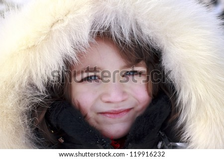 Close-up portrait of young girl wearing fur lined coat hood - stock photo