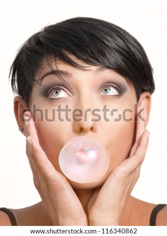 Close-up portrait of young girl with pink chewing gum on white background - stock photo