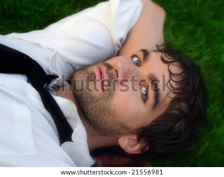 Close-up portrait of young good looking man in white shirt against grass - stock photo