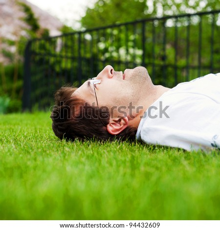 Close-up portrait of young good looking man in white shirt lying on lawn and daydreaming