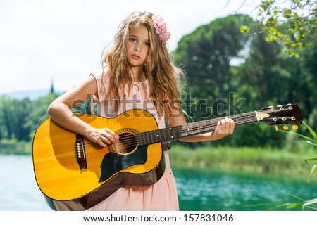 Close up portrait of young guitarist with spanish guitar at lake. - stock photo