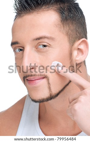 Close up portrait of young handsome man applying male cosmetic creme on face