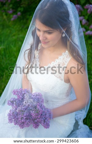 close up portrait of young happy beautiful bride in wedding dress with long veil - stock photo