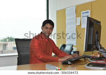 Close up portrait of Young Indian Man wearing Ethnic Indian Dress and working in high tech office on computer, India is leading in software development & other technology related business - stock photo