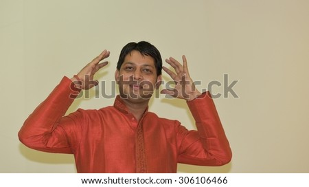 Close up portrait of Young Indian Man wearing Ethnic Indian Dress, Man is expressing to a good surprise, like winning a lottery - stock photo
