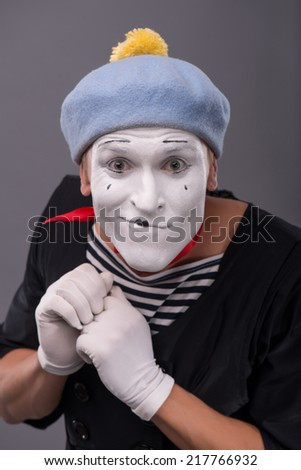 Close-up Portrait of young male mime with white face, grey hat insidiously scheming something and looking at the camera isolated on grey background  - stock photo