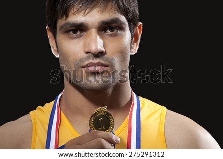 Close-up portrait of young male runner holding gold medal isolated over black background - stock photo