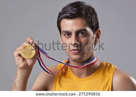 Close-up portrait of young man holding gold medal isolated over gray background - stock photo