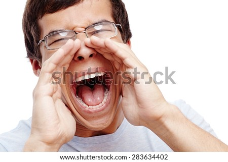 Close up portrait of young man in glasses yelling with open hands on isolated white background - stock photo