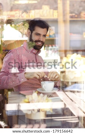 Close-up portrait of young man sitting at table in coffee shop. Shot behind the window.  - stock photo