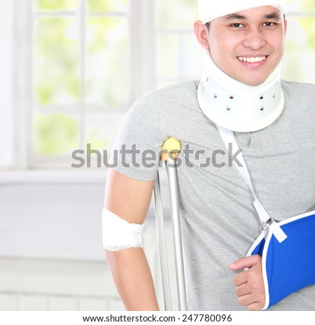close up portrait of young man use crutch and arm sling - stock photo