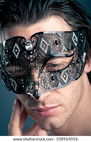 Close up portrait of young man with carnival mask against dark background.
