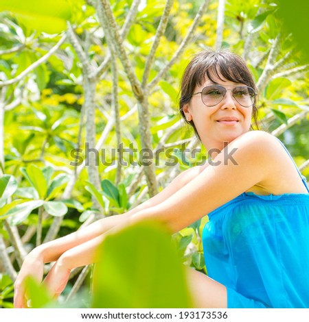 Close-up Portrait of young pretty woman with the blue dress and sunglasses sitting of the green national park  and looking at a camera - stock photo