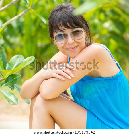 Close-up Portrait of young pretty woman with the blue dress and sunglasses sitting of the green national park  and looking at a camera