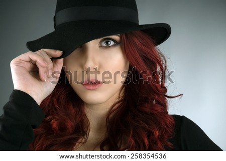 Close up portrait of young redhead posing with a hat isolated over gray background - stock photo