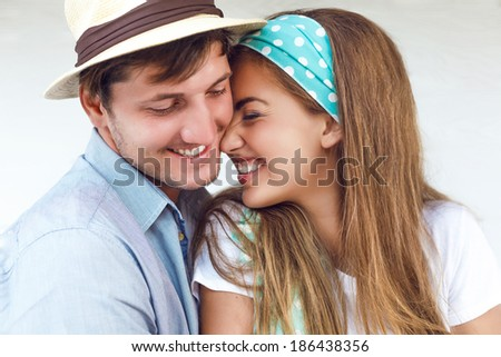 Close up portrait of young smiling beautiful couple in white background. - stock photo