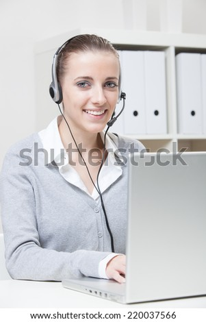 Close-up portrait of young smiling business woman with headset  - stock photo