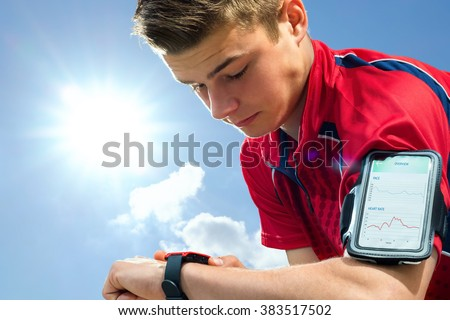 Close up portrait of young sports man reviewing activity tracker on smart watch. Teen boy wearing armband with smart phone against back light sun. - stock photo