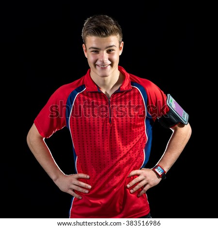 Close up portrait of young sports man wearing smart watch and armband with smart phone.Isolated against black background. - stock photo